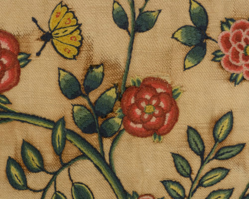 Detail of Pink flower with green stem embroidery. Yellow insect.