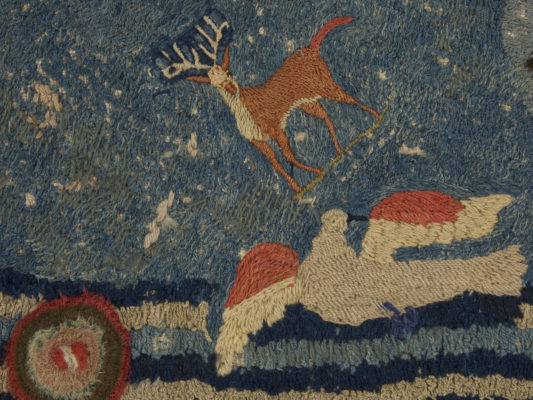 Detail of hearth rug, brown buck and flying dove.