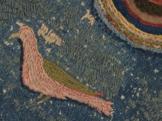 Detail of hearth rug, pink and green bird.