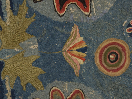 Detail of hearth rug. Flower, leaves, and concentric circles.