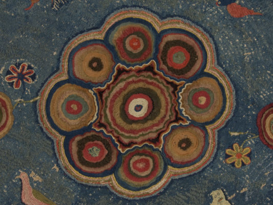 Detail of center of hearth rug with conjoined circular elements.