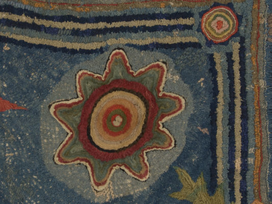 Detail of circle or sunburst in a corner of the hearth rug.