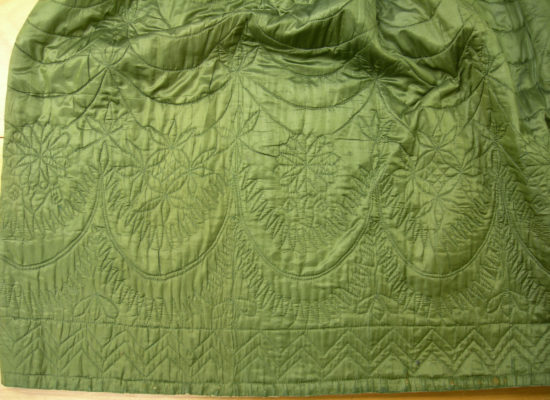 Detail of green petticoat's floral and geometric quilting.