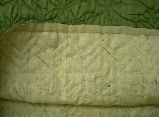 Detail of green petticoat's geometric quilting.
