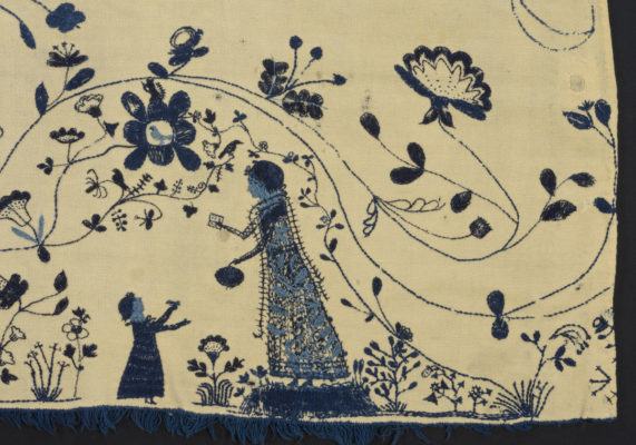 Front detail of embroidery featuring a woman and a child.