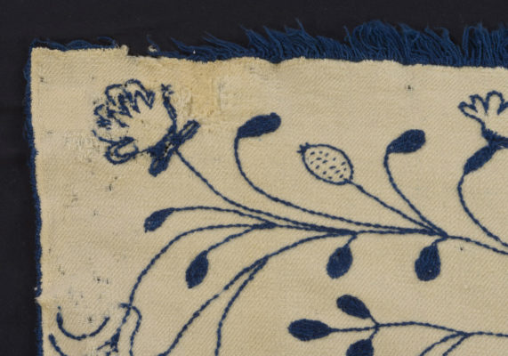 Detail of corner of embroidery, displaying wear.
