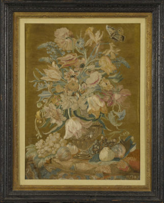 Framed needlework picture of a still life with flowers, fruit and a butterfly.