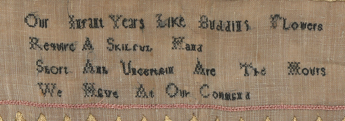Detail of sampler with embroidered phrase.