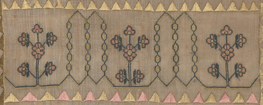 Detail of embroidery. Pink and yellow flowers flanked by yellow and green geometric design. Edged with pink and yellow triangle borders.