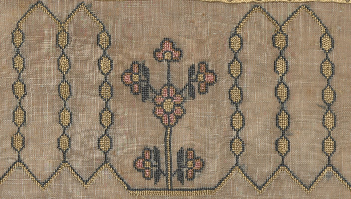 Detail of embroidery. Pink and yellow flowers flanked by yellow and green geometric design.