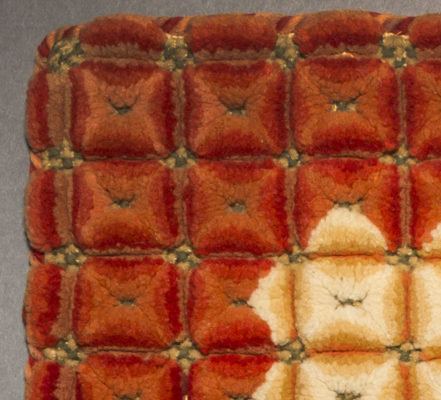 Detail of plush stitch cushion cover. Red, orange, yellow, and green.
