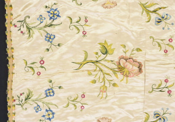 Detail of bed cover. Floral embroidery, pink and blue.