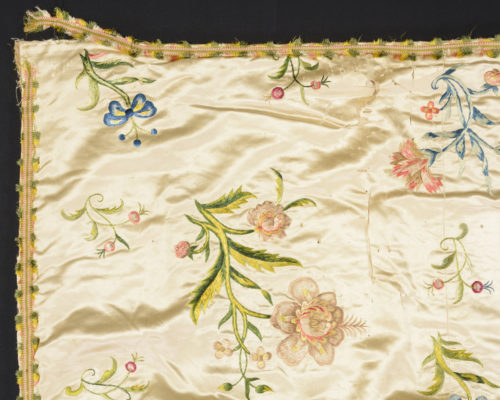 Detail of bedcover edge, displaying frayed trim and floral embroidery.