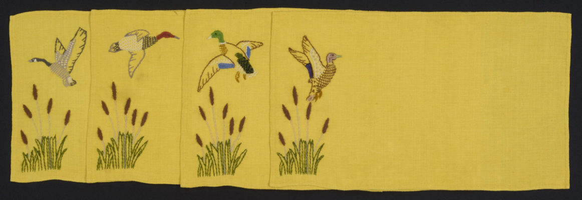 Four yellow place mats with crewelwork birds. Each placemat features one bird, either a goose or a duck, flying over cattails.