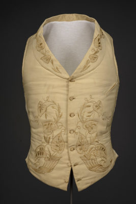 White embroidered waistcoat on a form.