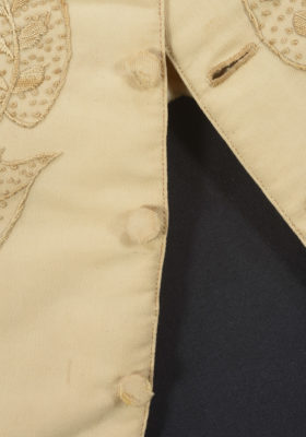 Detail of waistcoat. Features buttons, buttonhole, and some embroidery.