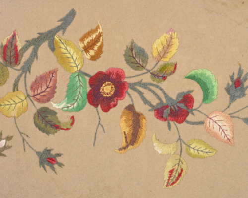 Detail of table cover featuring embroidered flowers, leaves, and vines.